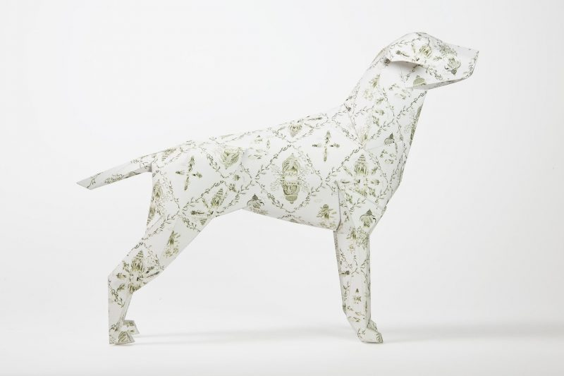 Side view of paper dog with a light coloured pattern on its coat with crosses.