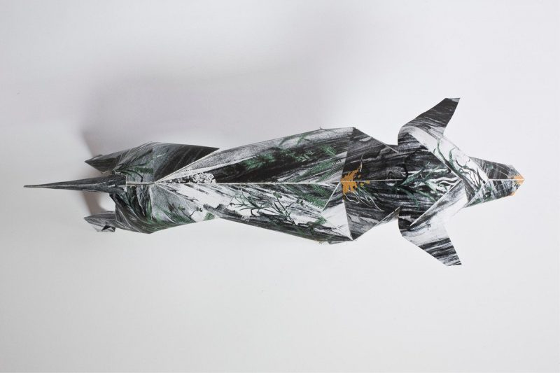 Overhead view of a paper dog model. Pattern is dark and misty like a winters night.