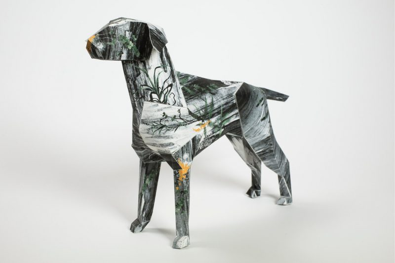 A paper dog sculpture by design studio Lazerian. A black and white sketchy design on its coat.