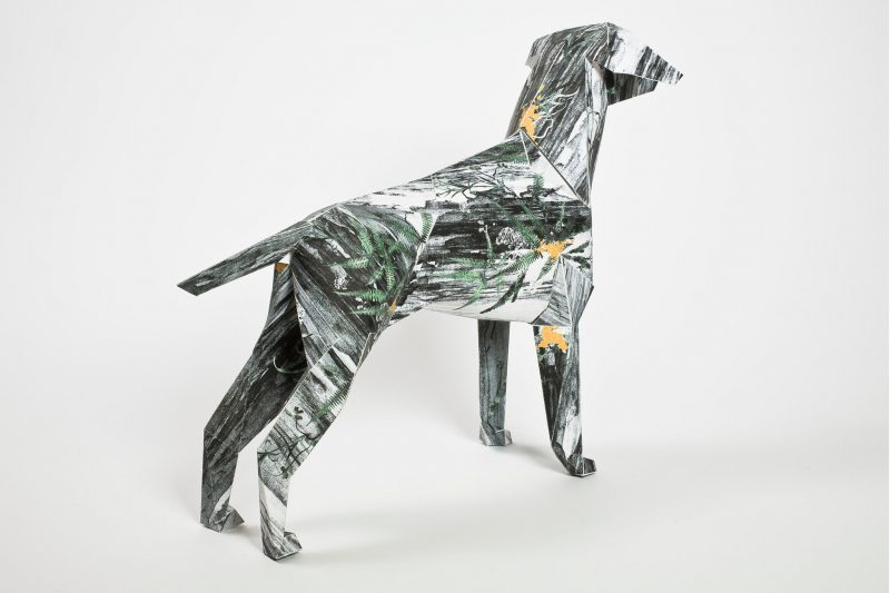 Model of a paper dog. The pattern on its coat is black and white with green speckles.