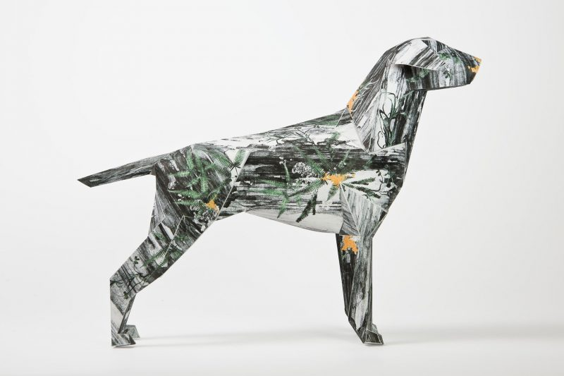A side view of a dog sculpture made from paper. It has a pattern on its coat- a monochrome sketchy pattern with speckles of green and orange.