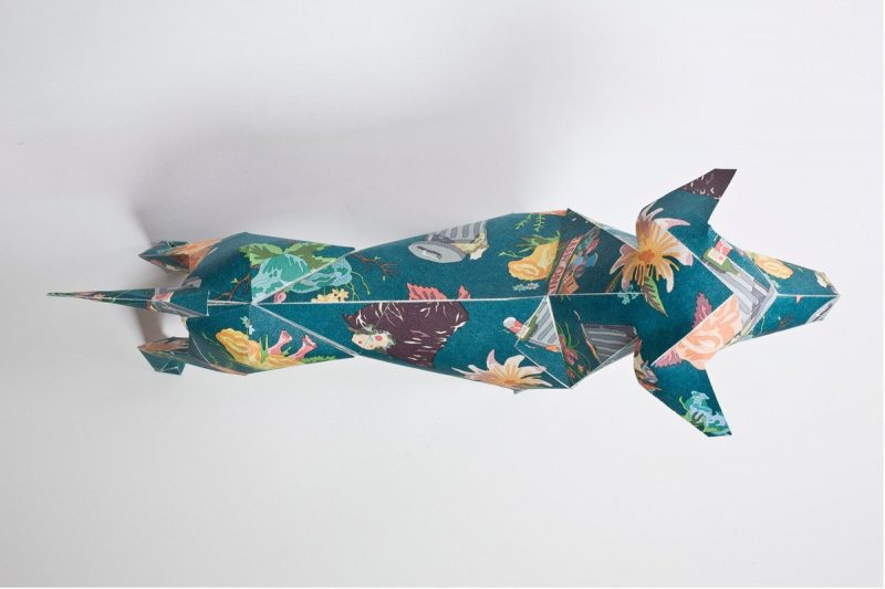 An over head view of a paper dog sculpture. It has a greem pattern with pastel flowers on its coat.