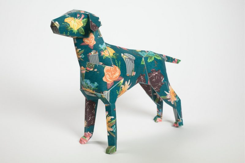 a dog model made using paper with a green pattern on its coat with pastel flowers.
