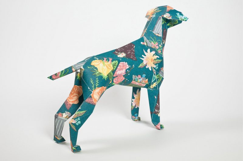 A paper dog model pointing with its head to the left side. The pattern on the dog is green with pastel flowers