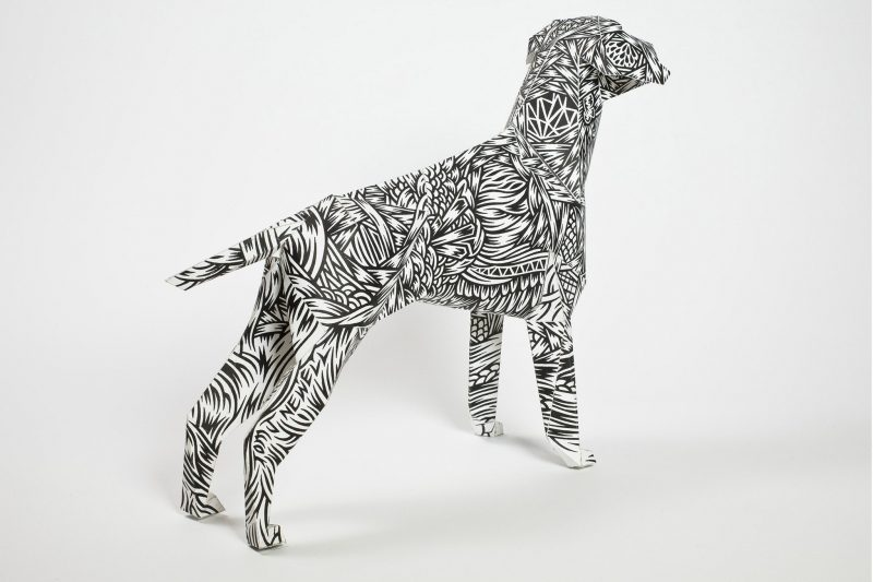 Right hand view of a dog model made from paper with a monochrome pattern on its coat