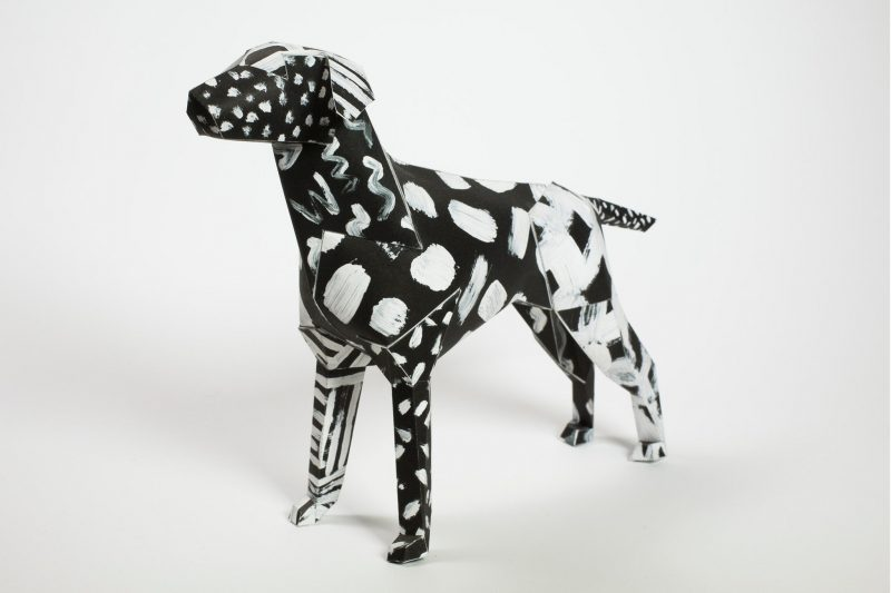 A paper dog model by design studio Lazerian. the pattern is a black background with white paint brush strokes over it