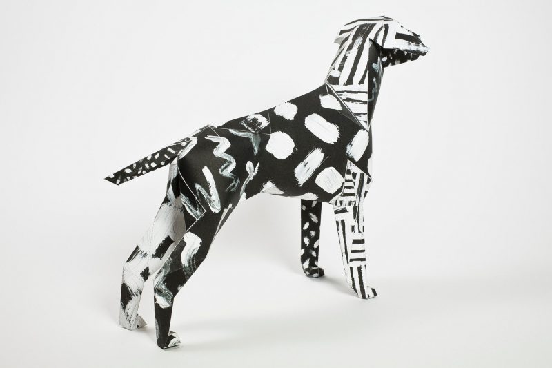 Paper dog model facing to the left hand side. A black background on the model with white paint strokes on it as well.