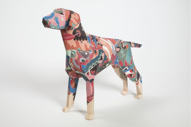 Left side view of a paper dog sculpture. The design on the coat is a pastel coloured camouflage print