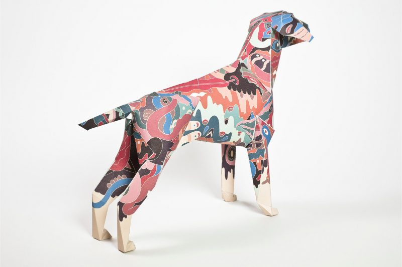 A pastel coloured type of camouflage print on a body of a paper dog model. The mascot of design studio Lazerian.