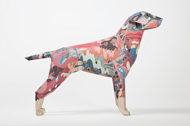A side view of a paper dog model- the pattern on the coat is a pastel camouflage print