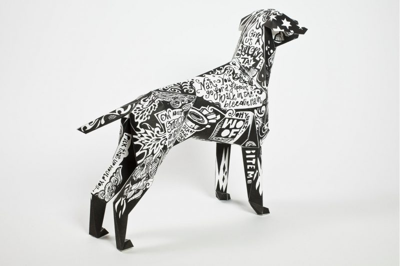 Paper dog model that is the mascot of Lazerian- a design studio from Manchester. The dog coat is black and white with white graffiti style writing on it