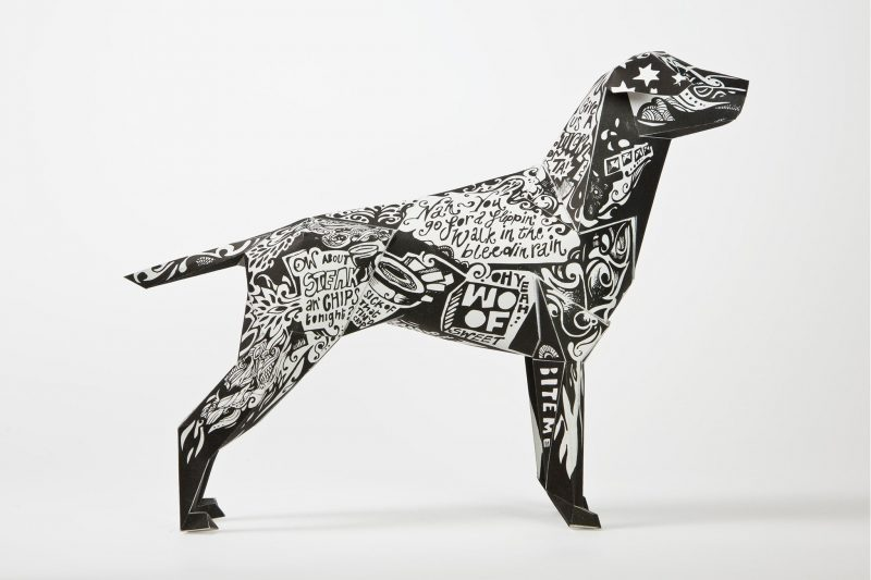 Side view of paper dog model. Has a black and white style designed coat