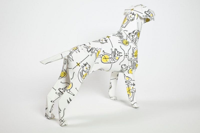 Paper dog model standing towards the right hand side and facing away from the camera. With a yellow and black pattern on its coat.