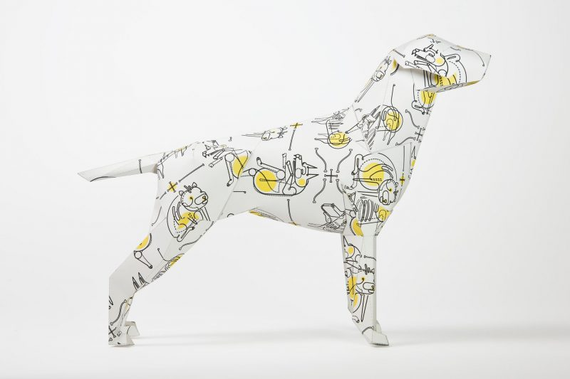 Yellow and black designed paper dog as part of an exhibition by design studio Lazerian. Dog coat pattern by will Scobie