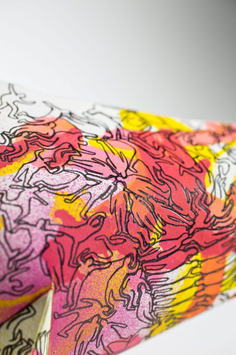 A close up view of a paper sculpture- it has a pattern on it with the silhouette of men in black and sploshes of reds, yellows, pinks and oranges.