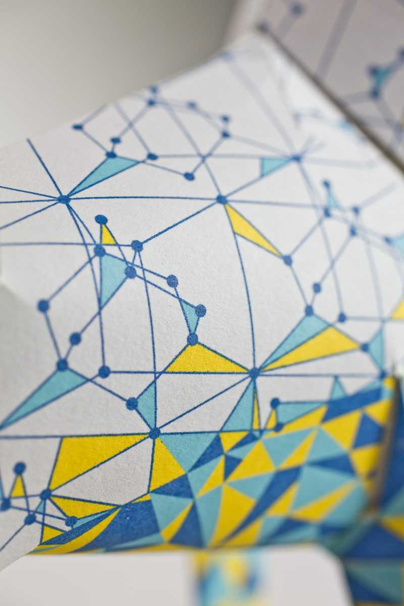 Close up of a design on a paper dog model. The design consists of lines connecting to make numerous different shaped and sized triangles. On the legs and the dogs face the triangles are sporadically filled with blues and yellows. Part of a design exhibition by Lazerian where artist and designers were invited to customise the dog sculptures. This dog was customised by Eskimo Creative of Manchester