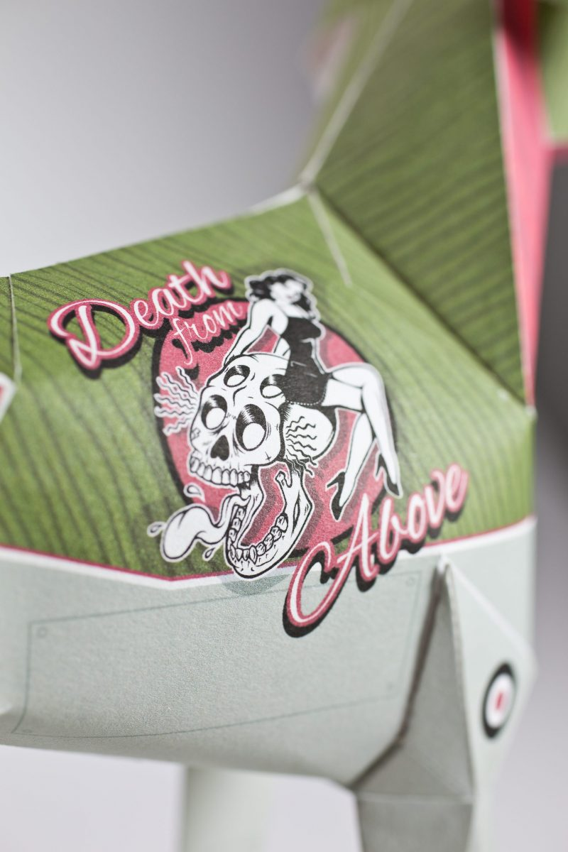 Close up of a paper dog model with a focus on the logo which is a 1950's woman in a bathing suit with the words 'Death from Above' wrote around her.