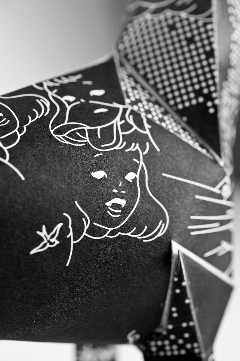 A close up of a design by DED on a paper dog model for an interantional exhibition by design leaders Lazerian. A 3D form of a paper dog sculpture the pattern is a black background with white line drawings of rabbits and ladies faces.