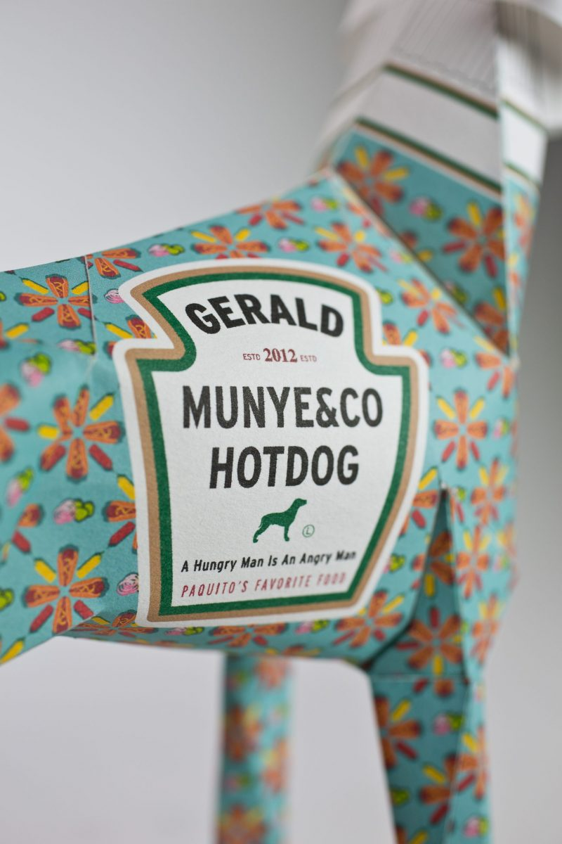 Close up view of 3D paper sculpture showing the logo it has designed on the dogs coat. It is a replica to the Heinz logo with the words substituted with GERALD MUNYE&CO HOTDOG you can also see a mint green background colour on the coat which is covered in orange flowers.