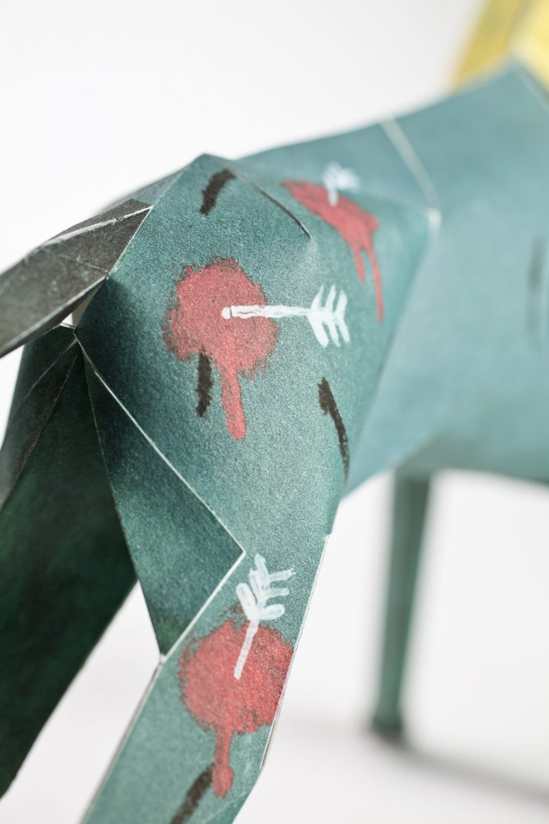 Close up of the backside of a paper dog model. Its green/blue with arrows and sploshes of reds to appear that its been shot at