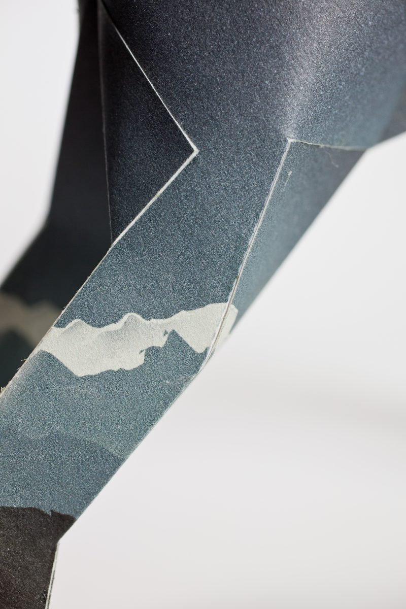 Close up of the leg of a paper dog sculpture which is part of a exhibition by leading design company Lazerian. It shows one leg with an illustration of a white mountain top on the background of a very dark navy blue nighttime sky colour. The exhibition invited designers and artists from around the world to customise the dog, which are also the mascot of Lazerian. This design is by Jack Hughes.