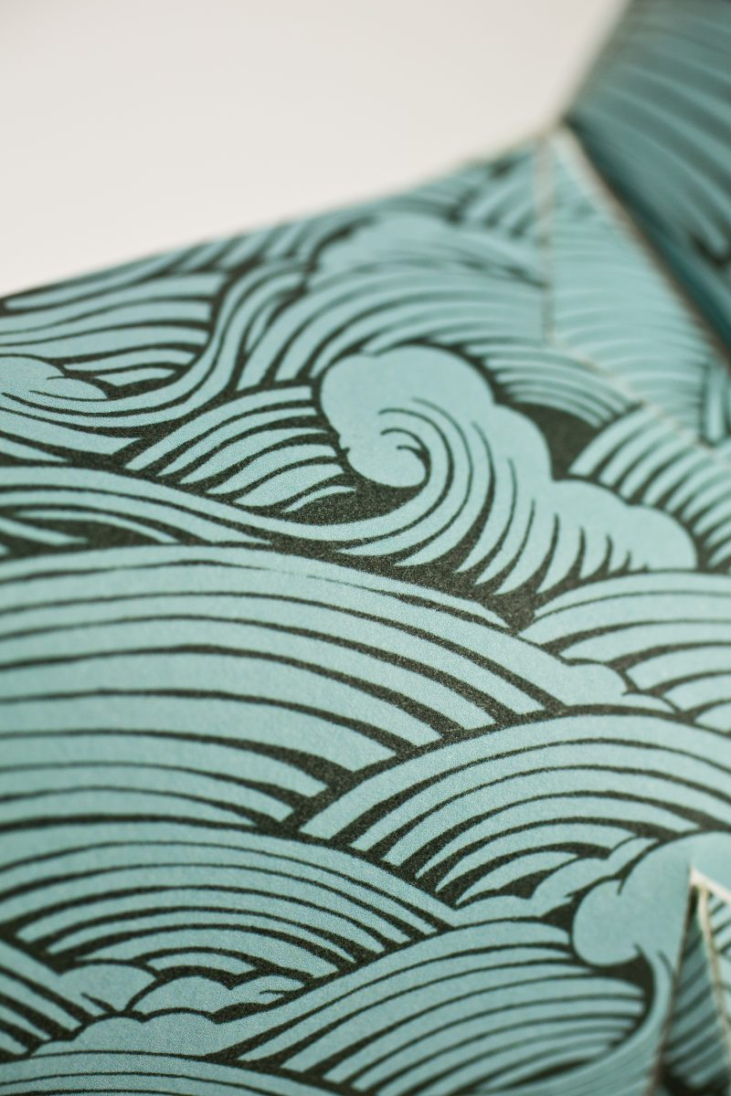 Close up view of a repeat wave pattern in a blue/green colour designed by artist Joe Wilson as part of an exhibition by design studio Lazerian. The dog is Lazerians studio mascot. The exhibition invited leading artists and designers to put their own stamp on the dog and create a design using their own signature styles.