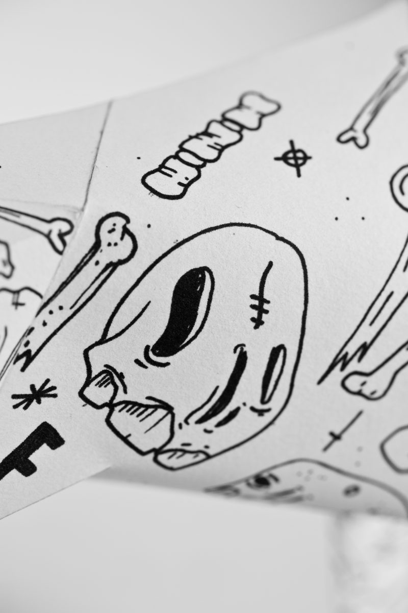 Close up of a black line drawing of skulls and bones on a white background of a paper dog sculpture in 3D form. Part of an exhibition from leading design studio Lazerian. The dog is the mascot of Lazerian and leading artist and designers were invited to showcase their original and signature dessigns onto the paper dog sculptures.