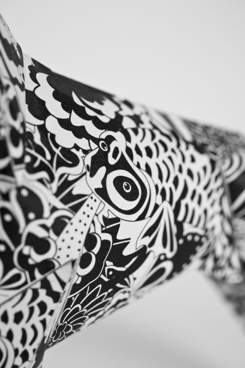 Close up of a black and white inspired by the 60's pattern. On a paper dog model in a 3D sculptural form. Designed by leading artist Grande Dame, it is part of an exhibition from leading designers and creators Lazerian.