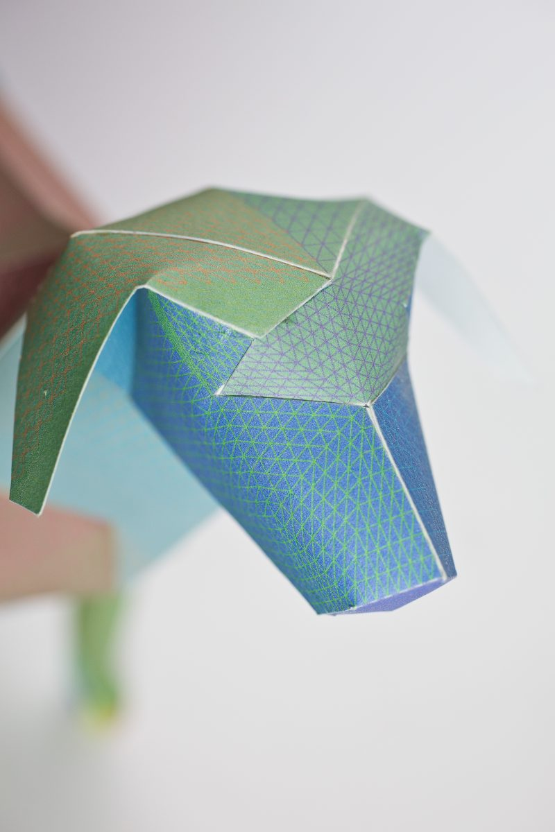 Close up of a paper dog sculpture by Atelier Doodle and design studio Lazerian. The dog is designed using greens, blues and brown colours. Part of a international exhibition of Gerald the Lazerian dog exhibition.