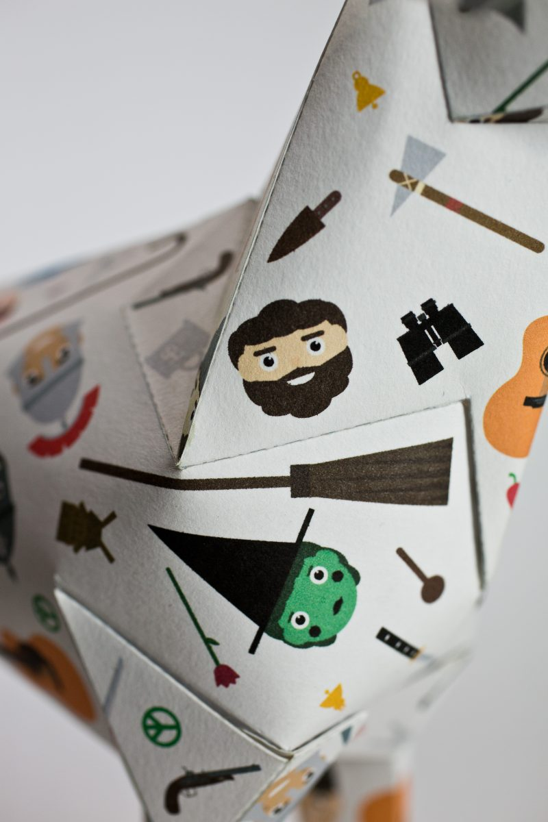 Close up of a paper dog design in a 3D sculptural form. The design on the coat is small faces of child like illustration of characters such as a green faced witch, a breaded man, a guitar etc. Part of a project by design studio Lazerian whose mascot is the paper dog. Lazerian wanted different styles of designers, creatives and artists to customise the paper dog sculptures using their own styles. this design is by children's illustrator Jamie Malone