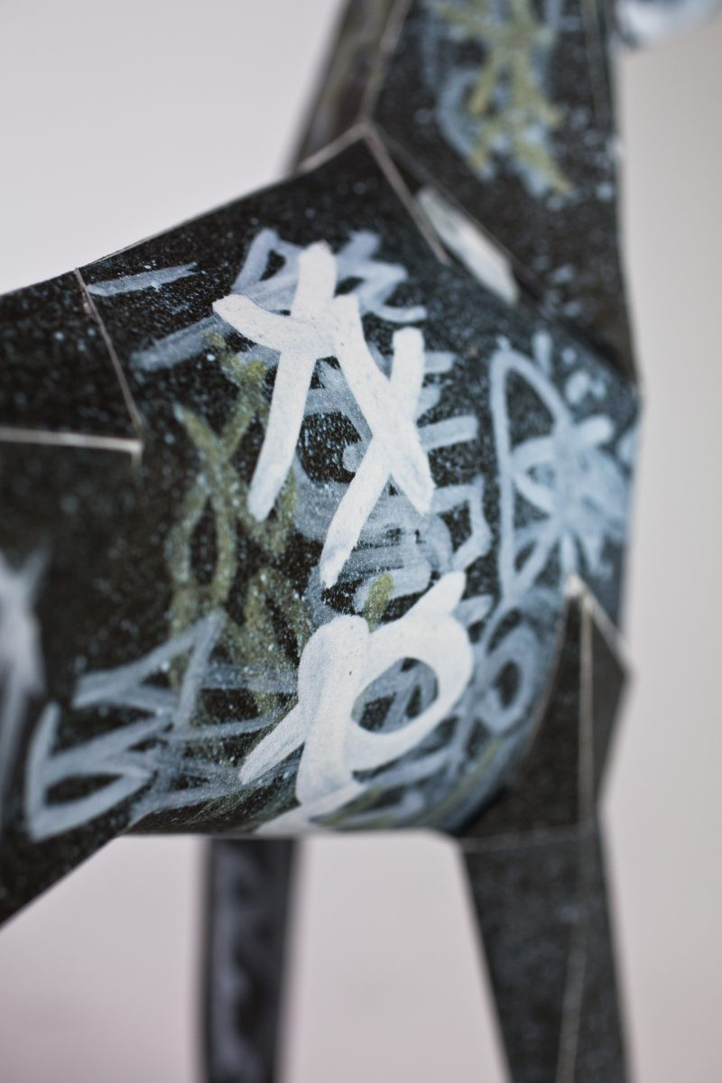 Close up of a black paper dog model in a 3D sculptural form. The dog has silver, white and gold graffiti scrawled all over it. Design by Dr.me and part of the international gerald exhibition by design leaders Lazerian