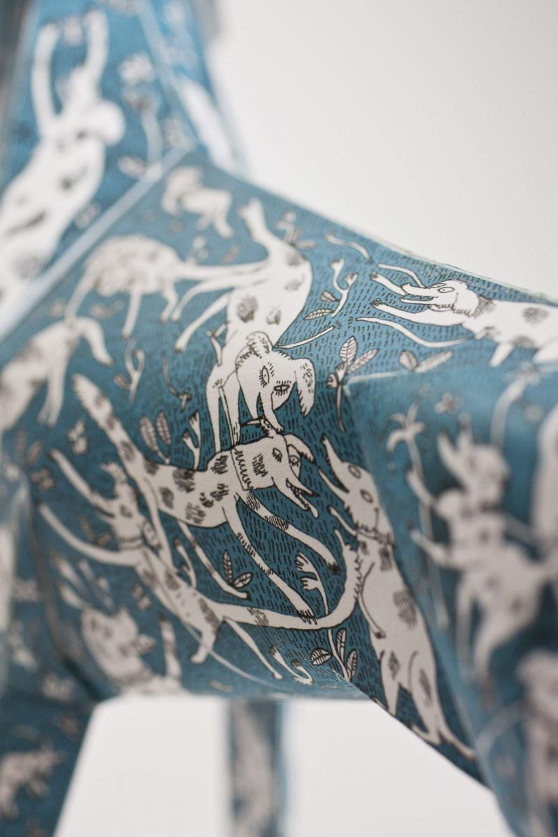 A close up view of a blue paper dog sculpture that has several white dogs drawn over it as a design feature.