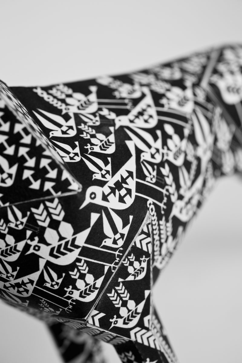 Close up of a black and white paper dog that was designed by Lesley Barnes, with white birds on it. For an international exhibition by design studio Lazerian