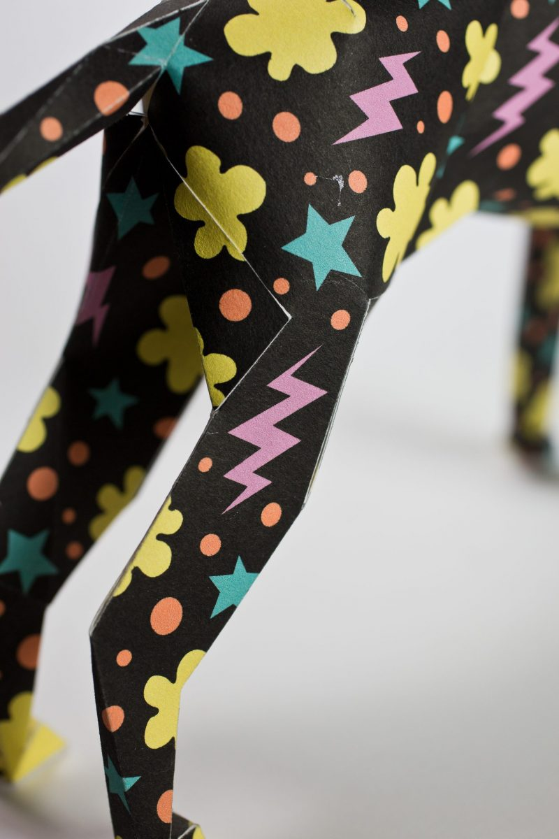 A close up view of a black paper dog model showing its back legs. They are covered in a design consisting of yellow cloud shapes, pink lighting bolts and blue stars.