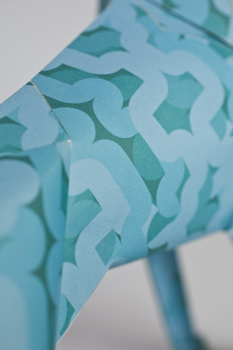 A close up of a light blue 60's style pattern on a paper dog. The dog is part of a exhibition by design studio Lazerian. Design by Alan Dalby,