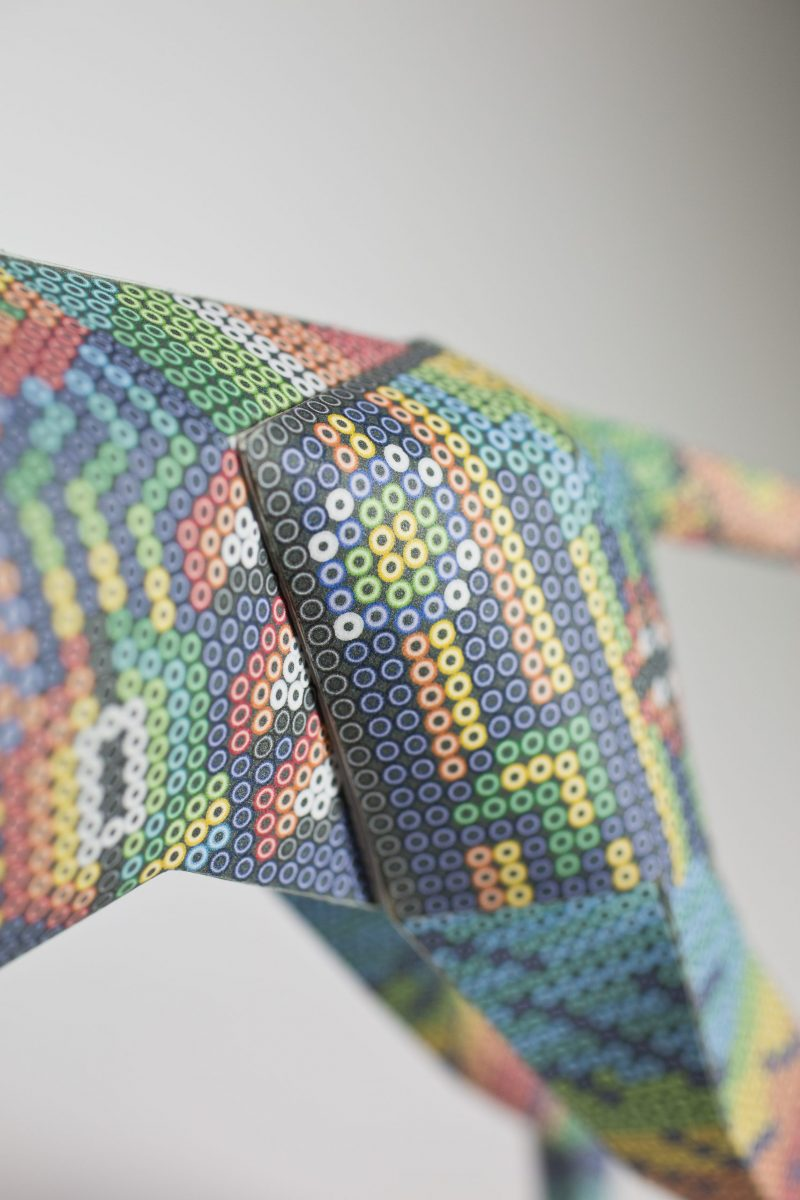 Close up view of a paper dog sculpture showing off the pattern which is Aztec style comprised of small colourful circles.
