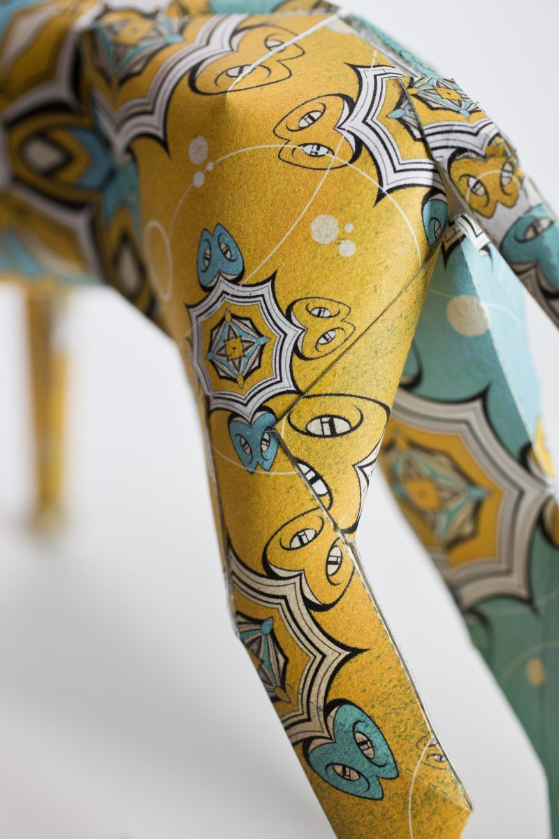 Close up of a paper dog sculpture with a yellow and blue pattern inspired by Egyptian lights from the artists time in Egypt. The artist is DBP Dave Bowcutt and it is part of a design exhibition from leading studio Lazerian