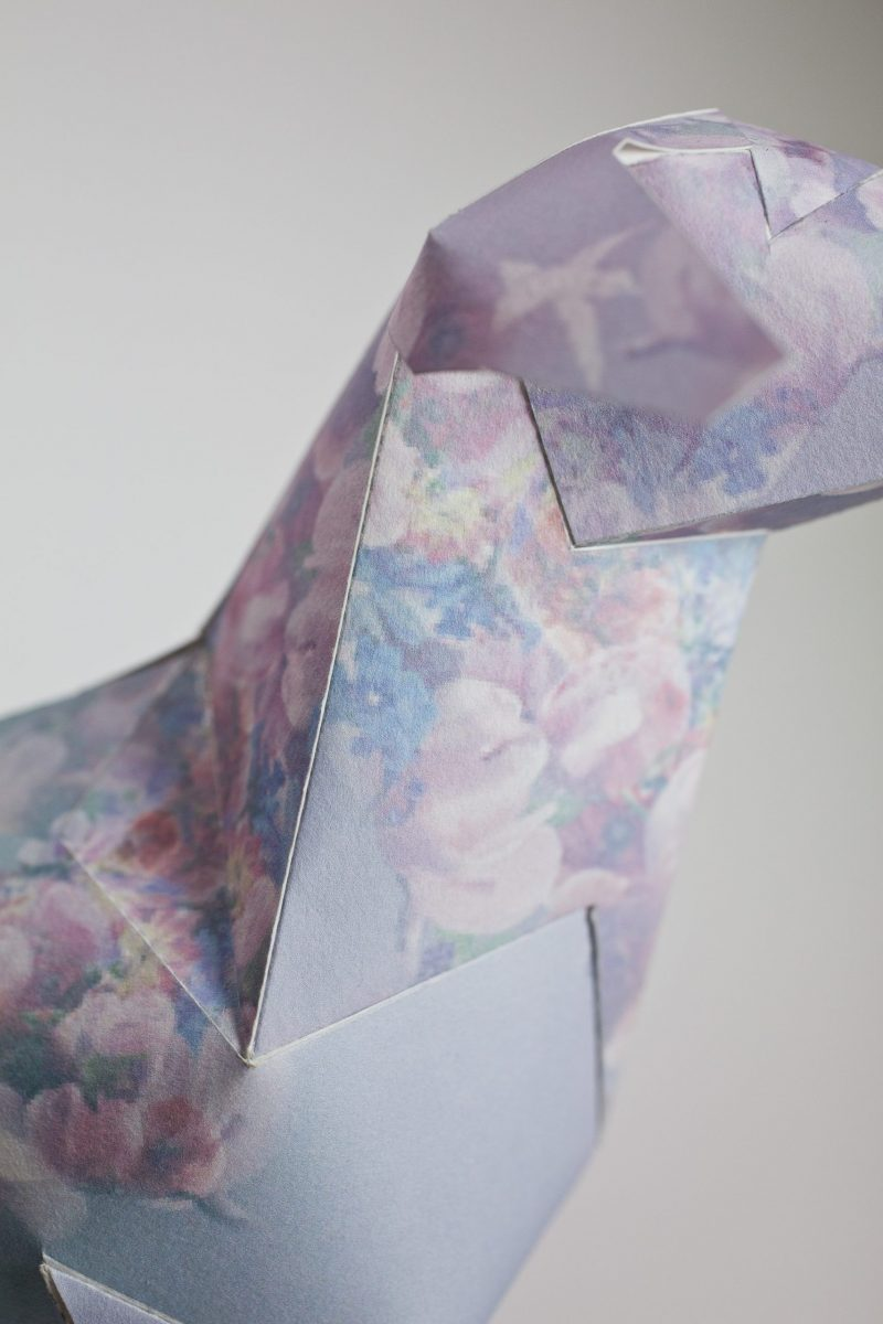 Close up view of a paper dog with pastel coloured pattern on its body.