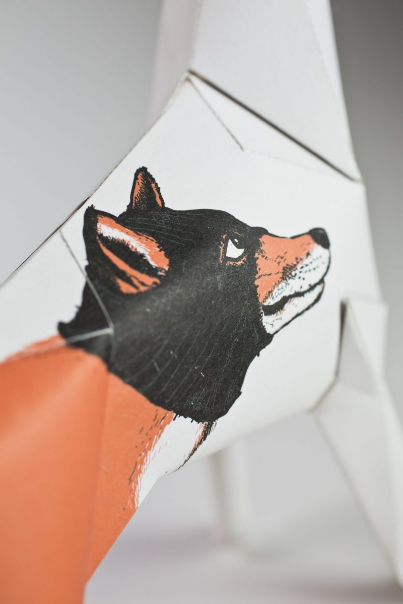 Close up of a paper dog model with a wolf face design on it