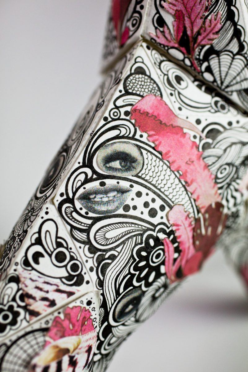 A close up pattern featuring black paisley pattern and pink marks