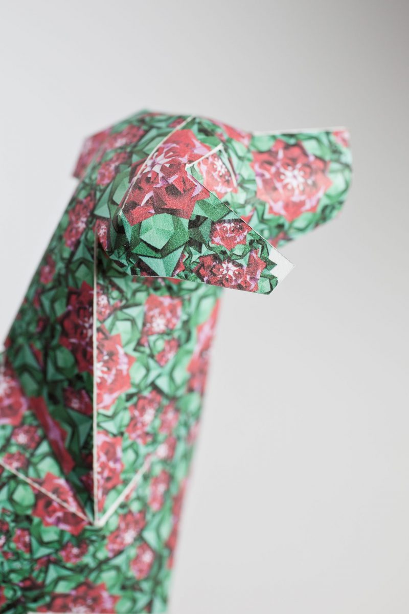 A close up of the head of a green paper dog sculpture with a design full of spring pink and red flowers on it.