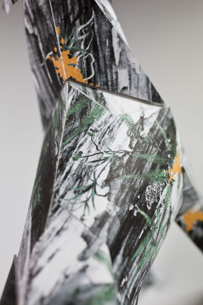 A close up of a patter on a paper dog model. It sis a dark sketchy pattern with specks of orange.