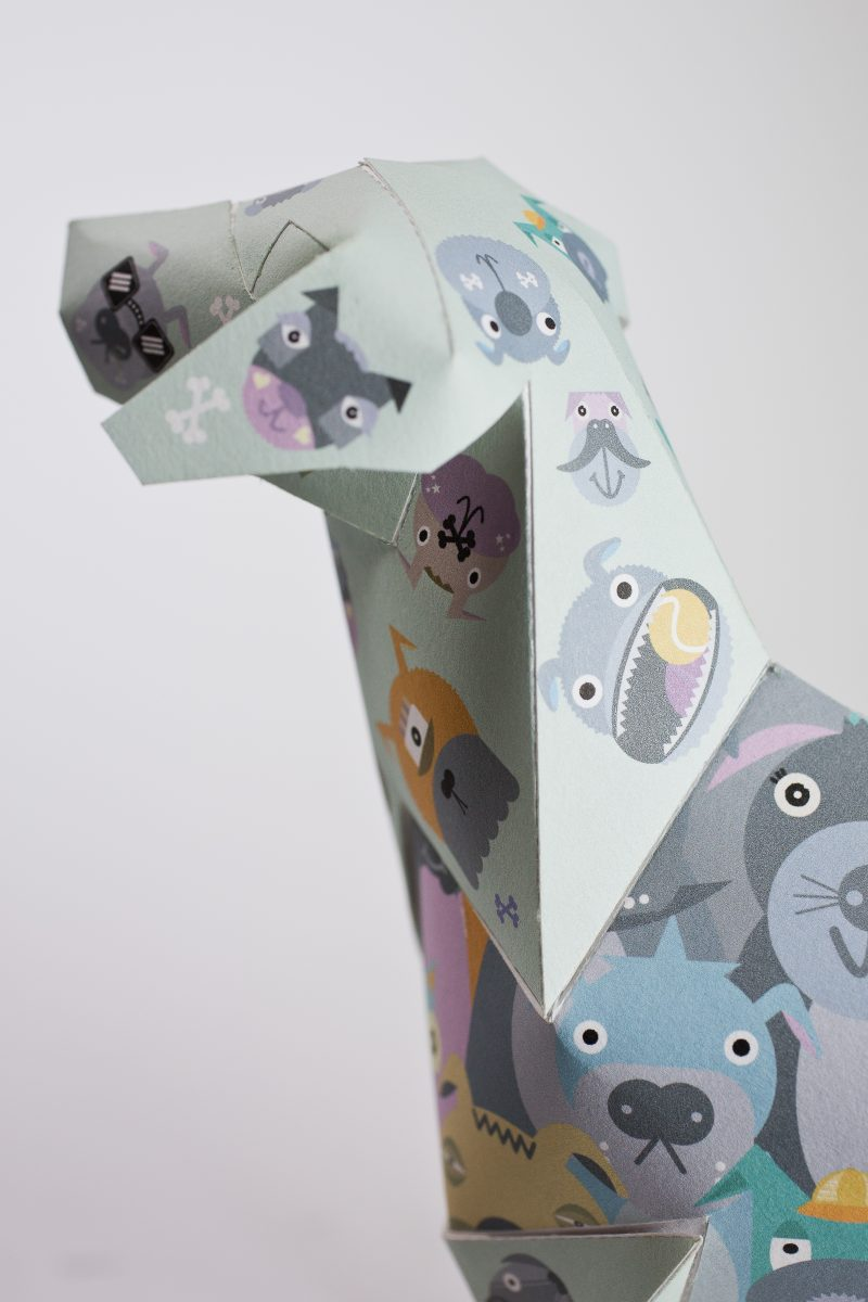 Close up of the face of a paper dog sculpture. It has illustrations of cute yellow and grey child like dogs all over it. designed by illustrator Kev Munday as part of an exhibition by design leaders LAzerian