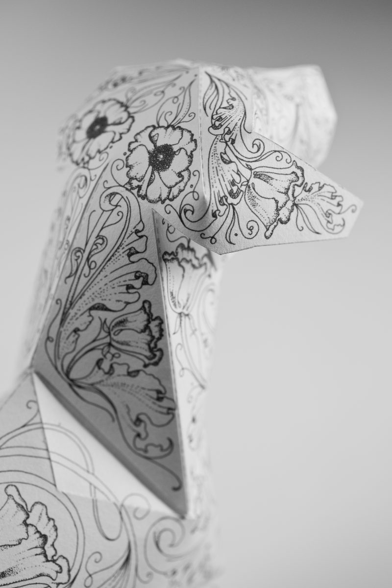 Close up of a paper dog model sculpture. PArt of a design exhibition by Lazerian with the repeating flower pattern being created by artist daren Newman