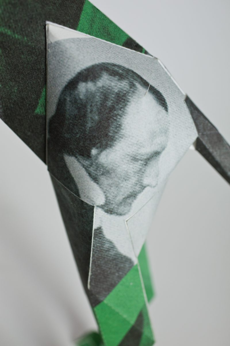 Close up of a leg of a paper dog model in 3D form. It shows a black and white image of an eldery man and a small green part on the leg. Part of a exhibition from Lazerian who invited several artists and designers to showcase their own unique design in their signature styles onto the paper dog sculptures. This design is from Hidden Leisure