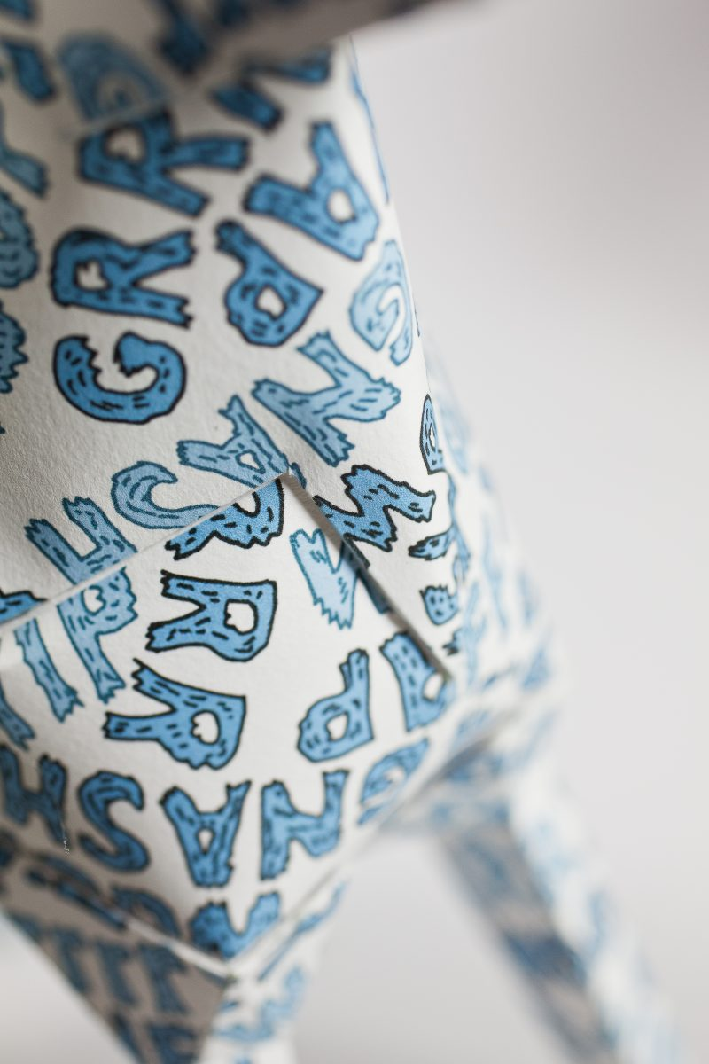 Close up of a white paper dog sculpture which is part of a design exhibition by Lazerian. The design on the dog is blue bubble lettering which says grr, ruff, woof and yap.