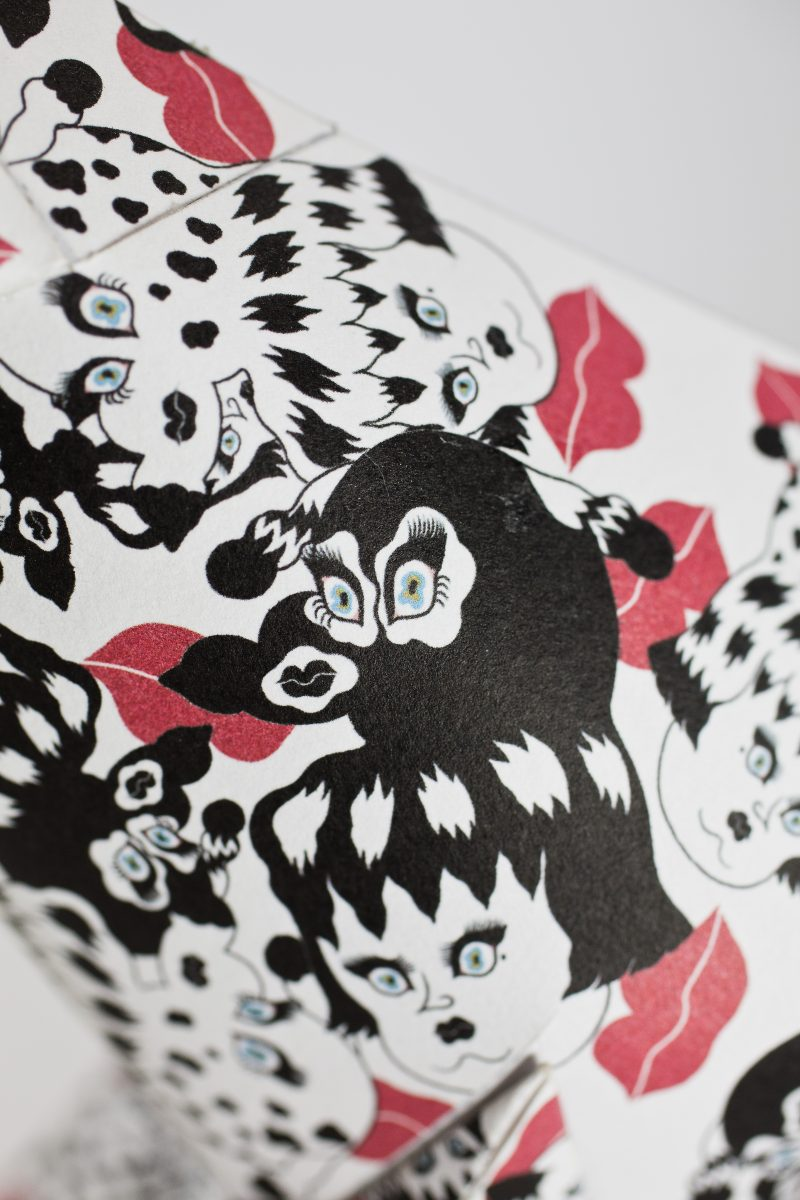 Close up of a black and white patterned paper dog sculpture with red lipstick marks on it. The design is by artist Jang Koal. Part of an international design exhibition by Lazerian