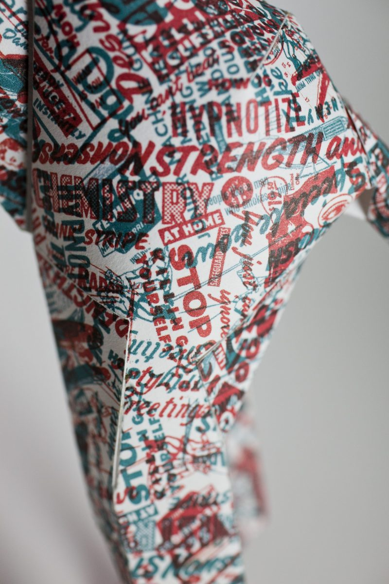 Close up of a newspaper style print pattern on the leg of a paper model dog sculpture. The random words are printed in red and blue.