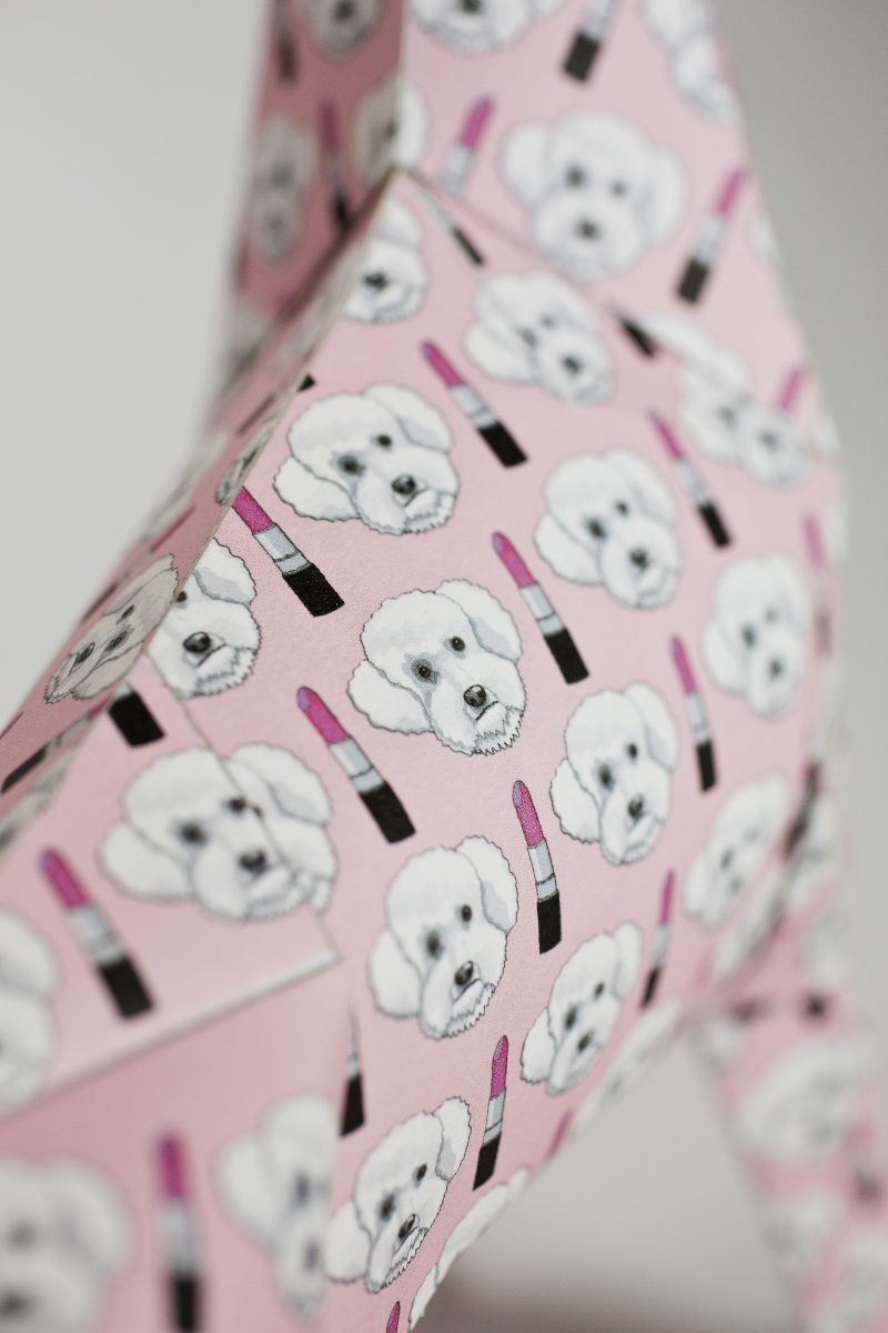 Close up of a baby pink paper sculpture from artist Grande Dame. Part of a design exhibition by designer lazerian. The paper dog is the mascot to the design studio and several designers and artists were asked to put their own designs on the coat of the paper dog.