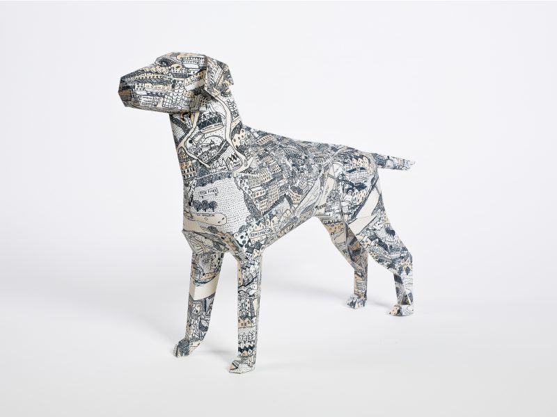 A paper dog model sculpture that is desined by David ryan robinson with a map pattern on it. Part of a design exhibition by designers Lazerian